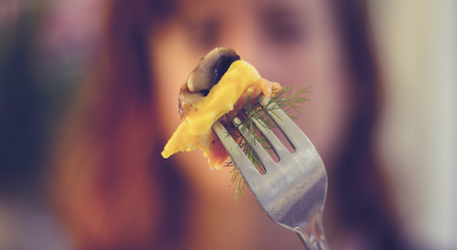 Woman holding a fork with food up in front of her face